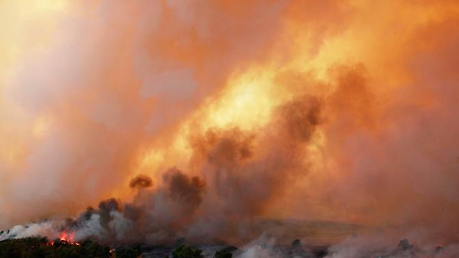 In this Saturday, Aug. 4, 2012 photo, flames burn near Highway 48 and HW 38 junction east of Drumright, Okla. The Oklahoma Department of Emergency Services says no injuries have been reported. (AP Photo/Tulsa World, Tom Gilbert)