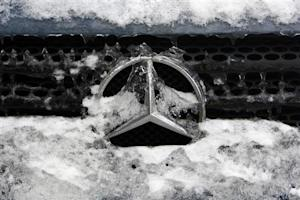 German car manufacturer Daimler's characteristic Mercedes-Benz star is seen covered with snow and ice on a vehicle in Bucharest