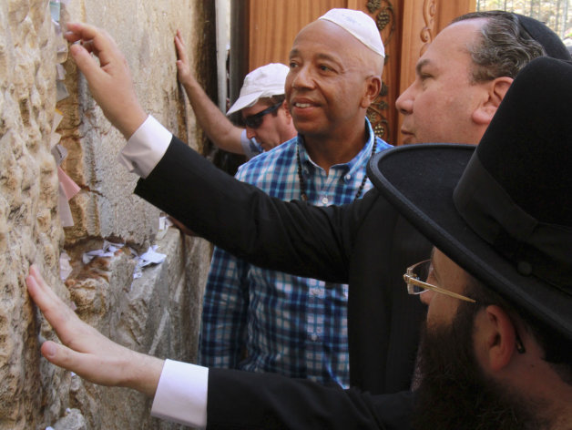 Hip hop mogul Russell Simmons, second left, looks on as US Rabbi Marc Schneier president and founder of the Foundation for Ethnic Understanding (FFEU), second right, and the Western Wall rabbi, Shmuel Rabinovich, right, touch stones of the Western Wall, the holiest site where Jews can pray, in Jerusalem's Old City, Thursday, June 21, 2012. The cofounder of the pioneering Def Jam Recordings record label, which has represented such artists like the Beastie Boys, Jay-Z, Lady Gaga, Jennifer Lopez, LL Cool J and Kanye West, is in Israel on the invitation of Israeli President Shimon Peres.(AP Photo/Blake Sobczak)