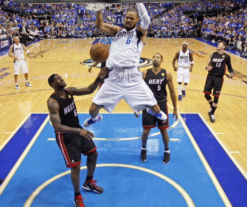 Dallas Mavericks' Tyson Chandler (6) dunks over Miami Heat's LeBron James (6) and Juwan Howard (5) during the first half of Game 5 of the NBA Finals basketball game Thursday, June 9, 2011, in Dallas. (AP Photo/Lucy Nicholson; Pool)