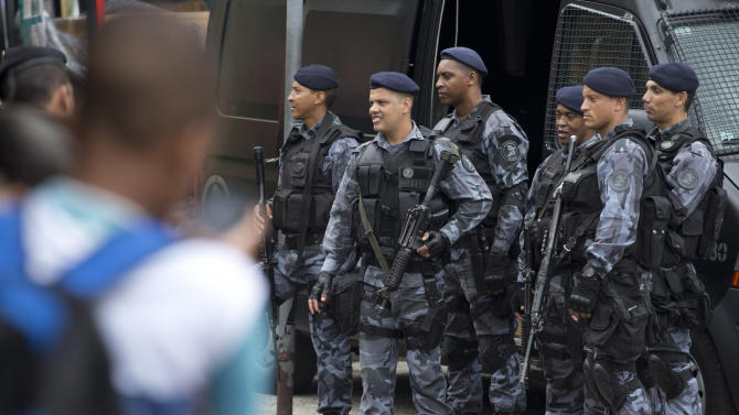 "Police officers stand guard at the Rocinha slum in Rio de Janeiro, Brazil, Monday, Feb.17, 2014. Police in Rio de Janeiro are reinforcing patrols in the Brazilian city's biggest slum after a weekend of shootouts. Rocinha is among Rio's ""pacified"" slums. In 2011, police entered and pushed the ruling drug gang out, and set up a permanent post. The slum pacification program is a key element of Rio's security plans ahead of this year's World Cup and the 2016 Olympics. (AP Photo/Silvia Izquierdo)"