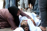 A relative grieves over a body brought to the Dera al-Shifa hospital in the northern city of Aleppo. Aid agencies say there is a mounting humanitarian crisis with more than 2.5 million people now needing help in the country