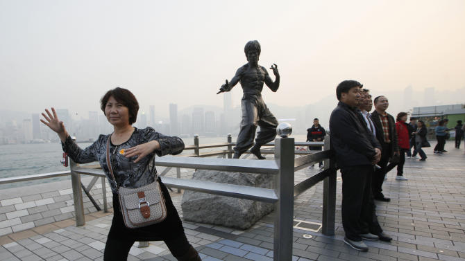 """In this Jan. 11, 2013 photo, Mainland Chinese tourists pose in front of a bronze statue of the Hong Kong martial art actor Bruce Lee on the Avenue of Stars, the city's version of the Hollywood Walk of Fame in Hong Kong. He's arguably Hong Kong's most famous movie star but the city has done little to commemorate Bruce Lee, who shot to global stardom with films like """"Enter the Dragon"""" but died in 1973 at age 32 of swelling of the brain. (AP Photo/Kin Cheung)"""