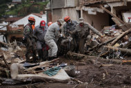 Rescue workers remove the body of a landslide victim in Nova Friburgo in Rio de Janeiro state, Brazil, Saturday Jan. 15, 2011. After four nights of torrential rains, mudslides have killed more than 500 people in the Rio de Janeiro area.