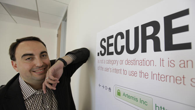 "In this photo taken Friday, June 8, 2012 Alex Stamos CTO of Artemis Internet, an NCC Group Company, poses by a domain name poster at their offices in San Francisco. Some 2,000 proposals have been submitted as part of the largest expansion of the Internet address system since its creation in the 1980s. These suffixes would rival "".com"" and about 250 others now in use. The organization behind it, the Internet Corporation for Assigned Names and Numbers, will announce a full list and other details in London on Wednesday. (AP Photo/Eric Risberg)"