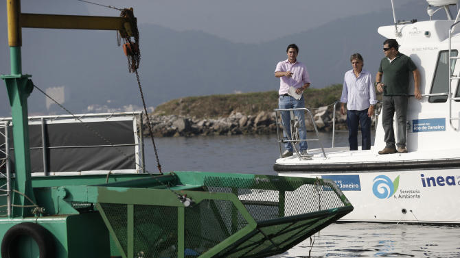 """Rio de Janeiro's Sub Secretary of Environment Carlos Portinho, left, inspects the water in front of an """"eco-boat"""" in Guanabara Bay in Rio de Janeiro, Brazil, Thursday, April 10, 2014. The barge is one of three so-called """"eco-boats,"""" floating garbage vessels that are a key part of authorities' pledge to clean up Rio's devastated Guanabara Bay before the city – and the waterway itself – plays host to the 2016 Olympic games. (AP Photo/Silvia Izquierdo)"""