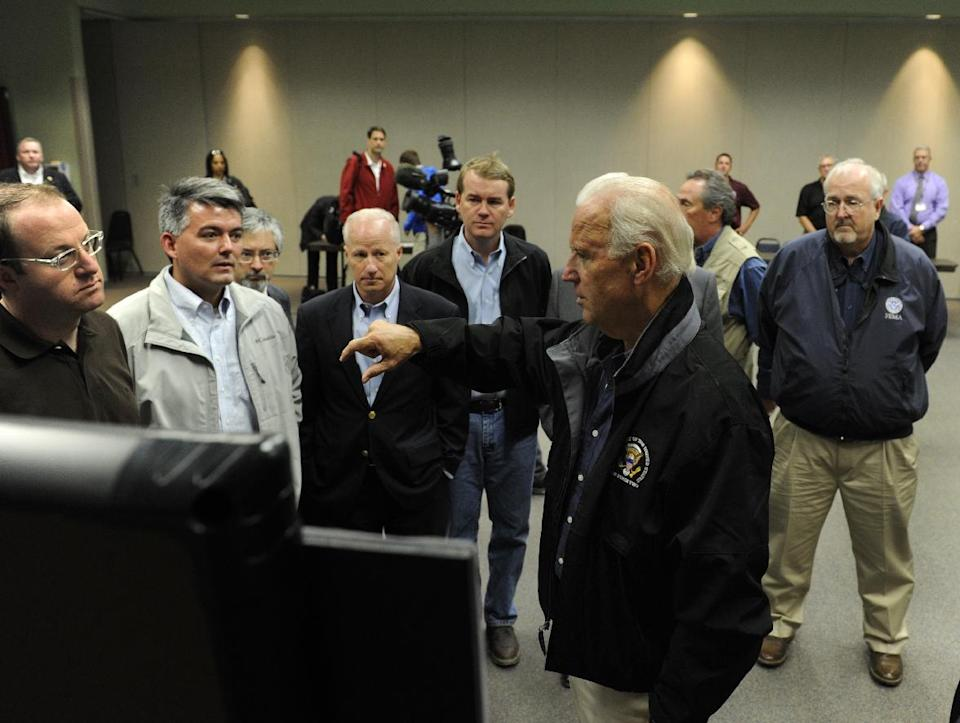 After flying in a helicopter over areas ravaged by the recent flooding, Vice President Joe Biden, center front, flanked by Colorado elected officials and FEMA workers, looks at maps of the areas that were hit, Monday, Sept. 23, 2013, in Greeley Colo. (AP Photo/The Denver Post, Kathryn Scott Osler, Pool)