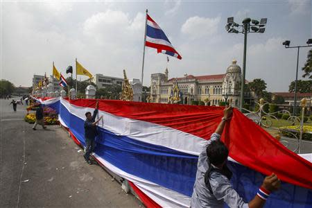 Anti-government protesters place a large Thai national flag around Government House in Bangkok