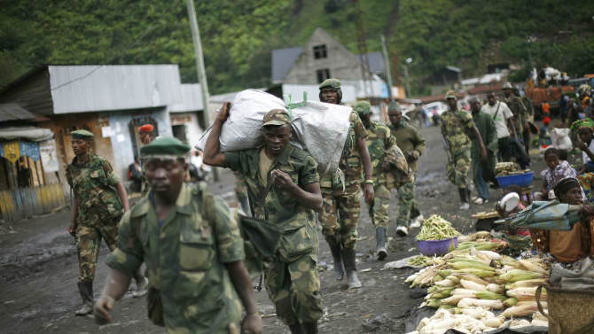 "FILE - In this Nov. 30, 2012 file photo, M23 rebels withdraw from the Masisi and Sake areas in the eastern Congo town of Sake, some 27 kms west of Goma, Congo. A Congolese rebel group whose fighters retreated into Uganda after being hammered by U.N.-backed Congolese government forces ""can still regroup,"" a Ugandan government spokesman said Tuesday, Nov. 12, 2013. The warning came after Congolese government officials delayed signing a peace accord with the insurgents. (AP Photo/Jerome Delay, File)"