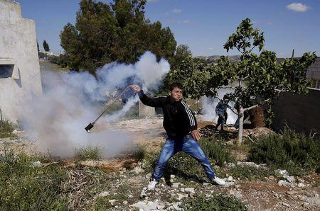 A Palestinian protester uses a sling to return a tear gas canister fired by Israeli troops during clashes following a protest against Jewish settlements in Nabi Saleh