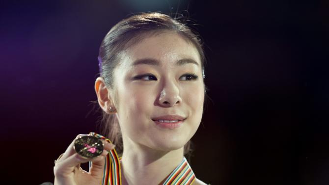 Kim Yu-na from South Korea holds up her gold medal during victory ceremonies at the World Figure Skating Championships Saturday, March 16, 2013 in London, Ontario. (AP Photo/The Canadian Press, Paul Chiasson)