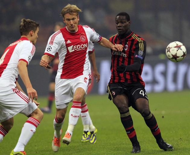 AC Milan's Balotelli fights for the ball with Ajax Amsterdam's Poulsen and Moisander during their Champions League group H soccer match in Milan
