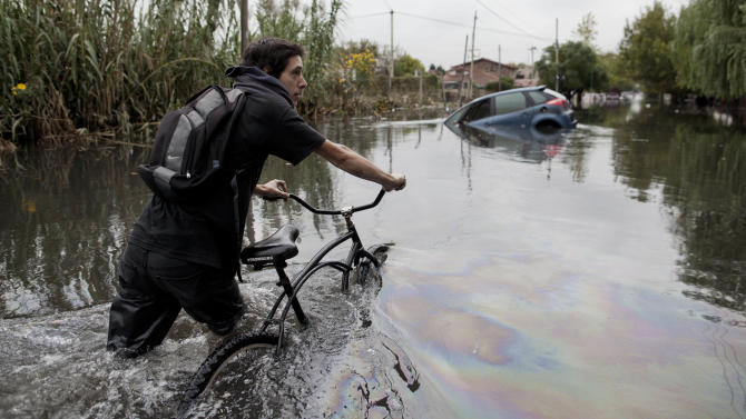A man pushes his bike through a flooded street in La Plata, in Argentina's Buenos Aires province, Wednesday, April 3, 2013. At least 35 people were killed by flooding overnight in Argentina's Buenos Aires province, the governor said Wednesday, bringing the overall death toll from days of torrential rains to at least 41 and leaving large stretches of the provincial capital under water. (AP Photo/Natacha Pisarenko)