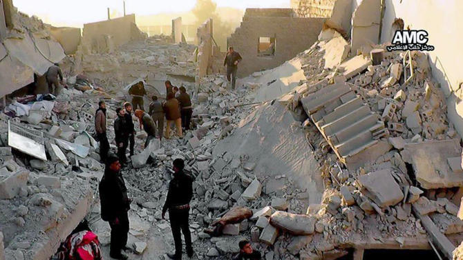 In this Monday, Jan. 6, 2013 citizen journalism image provided by Aleppo Media Center, AMC, which has been authenticated based on its contents and other AP reporting, Syrians inspect the rubble of destroyed buildings following a Syrian government airstrike in Aleppo, Syria. Syrian rebel groups battled one another Monday for control of a provincial capital, part of a vicious round of score settling targeting an al-Qaida affiliate that gained stature fighting President Bashar Assad but alienated many by imposing strict Islamic law. (AP Photo/Aleppo Media Center AMC)