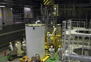 Workers wearing protective suits and masks work on a crane for a transport container inside the No. 4 reactor building in Fukushima