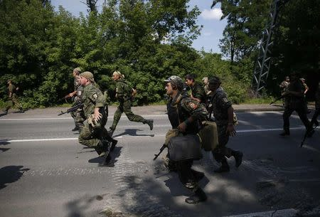 Pro-Russian separatist fighters from the so-called Battalion Vostok (East) run into position at a checkpoint in Donetsk