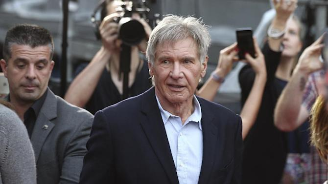 """FILE - In this December 10, 2015 file photo Harrison Ford walks during a Star Wars fan event in Sydney. Ford is in Australia to promote his latest film """"Star Wars: The Force Awakens"""". British health authorities said on Thursday Feb. 11, 2016 that criminal charges have been laid against producers of """"Star Wars: The Force Awakens"""" over an on-set accident in which Harrison Ford broke his leg. (AP Photo/Rob Griffith, File)"""