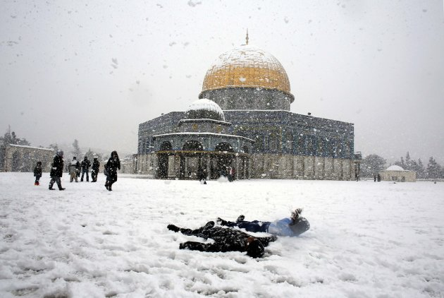 Children play in front of the Dome on the Rock during the recent snowstorm in Israel; Photo from Reuters/Ammar Awad