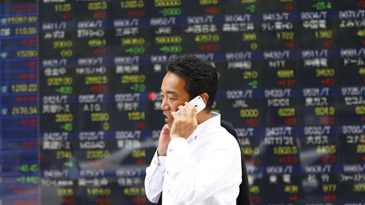 A man speaks on a mobile phone in front of an electronic stock indicator in Tokyo, Tuesday, July 22, 2014. Asian shares rose Tuesday as tensions over the downing of a passenger jet in Ukraine eased after pro-Moscow separatists released a train packed with bodies and handed over the aircraft's black boxes. Japan's Nikkei 225 stock index added 0.8 percent to 15,343.28 as trading resumed after Monday's public holiday. (AP Photo/Shizuo Kambayashi)