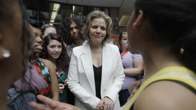 In this March 19, 2012 photo, famed soprano Renee Fleming talks to the students after performing with a choir of dozens of high school students in the rotunda of the State of Illinois building, the James R. Thompson Center, in Chicago. For the past school year the opera singer has been mentoring teenaged vocal students in Chicago as part of her role as creative consultant at the Lyric Opera of Chicago.(AP Photo/Kiichiro Sato)