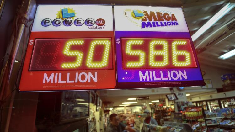 A worker at Nick's Liquor Store sells lottery tickets as a sign shows the Mega Millions jackpot estimated at $586 million in Venice, California