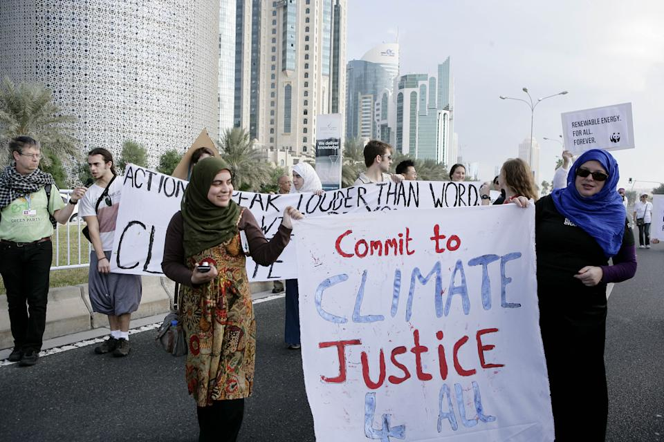 "Qatari Women activists holding a banner reading ""commit to climate justice 4 all "" as they march with local and international activists march to demand urgent action to address climate change at the U.N. climate talks in Doha, Qatar, Saturday , Dec. 1, 2012. (AP Photo/Osama Faisal)"