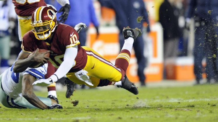 Washington Redskins quarterback Robert Griffin III (10) dives past Dallas Cowboys cornerback Brandon Carr (39) during the first half of an NFL football game Sunday, Dec. 30, 2012, in Landover, Md. (AP Photo/Nick Wass)