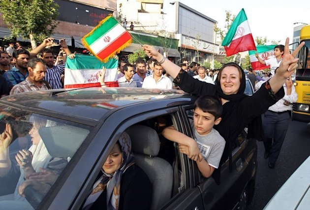 Football fans celebrate at Vanak square in northern Tehran on June 18, 2013 after Iran qualified for the 2014 World Cup