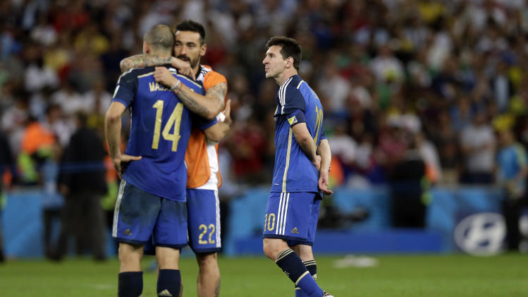 Argentina's Lionel Messi, right, walks over the pitch as his teammate Ezequiel Lavezzi hugs Javier Mascherano after the World Cup final soccer match between Germany and Argentina at the Maracana Stadium in Rio de Janeiro, Brazil, Sunday, July 13, 2014. Germany beat Argentina 1-0 to win its fourth World Cup title. (AP Photo/Victor R. Caivano)