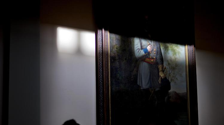 In this Thursday, Jan. 3, 2013 file photo, a clerk walks past a portrait of Confederate Gen. Robert E. Lee in the rotunda of the Georgia State Capitol in Atlanta. (AP Photo/David Goldman)