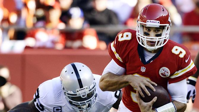"""Kansas City Chiefs quarterback Brady Quinn (9) is tackled by Oakland Raiders defensive tackle Tommy Kelly (93) during the first half of an NFL football game at Arrowhead Stadium in Kansas City, Mo., Sunday, Oct. 28, 2012. Quinn left the game during the first quarter due to what the team called a """"head injury."""" (AP Photo/Reed Hoffmann)"""