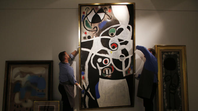 """FILE - In this Thursday, Dec. 19, 2013 file photo, auction house workers adjust Joan Miro's 1968 oil painting """"Women and Birds"""" which has an estimated sale price of 4-to-7 million pounds ($6.5 million to $11.5 million), in a room with other works by Miro, at Christie's auction house in central London. Portugal is hoping a master of surrealism can help taxpayers recoup some of the millions they lost rescuing a failed bank. The government is selling 85 works by Spanish artist Joan Miro that became public property when Banco Portugues de Negocios was nationalized in 2008. Christie's in London, which is handling the two-day sale starting Tuesday, Feb. 4, 2014, describes the collection as """"one of the most extensive and impressive offerings of works by the artist ever to come to auction."""" (AP Photo/Lefteris Pitarakis, File)"""