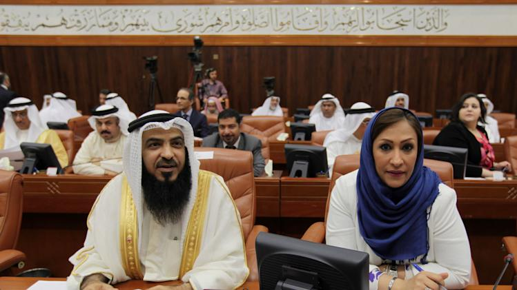 Bahraini lawmaker Adel al-Moawdeh of the Islamic Salafist al-Asalah bloc, left, and Sawsan Taqawi, an independent, right, participate in a special session of parliament to discuss how to handle the uprising in the Gulf island kingdom, convened in Manama, Bahrain, Sunday, July 28, 2013. Several members of Bahrain's parliament, which doesn't include opposition groups, called for harsher methods against protesters, including stripping citizenship, establishing curfews, instituting martial law, employing the death penalty and banning all protests. (AP Photo/Hasan Jamali)