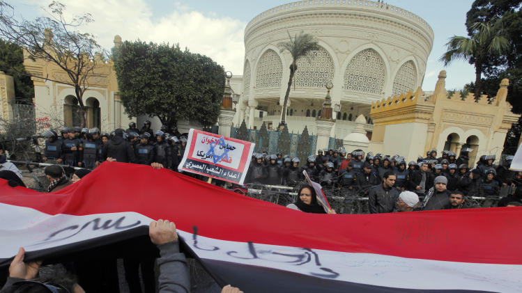 "Egyptians wave a giant flag during anti-President Mohammed Morsi protest in front of the presidential palace in Cairo, Egypt, Friday, Feb. 1, 2013. Arabic reads ""Hamas, brotherhood, Qatar and America, are Egyptian enemies."" Thousands of Egyptians marched across the country, chanting against the rule of the Islamist President Mohammed Morsi, in a fresh wave of protests Friday, even as cracks appeared in the ranks of the opposition after its political leaders met for the first time with the rival Muslim Brotherhood.(AP Photo/Amr Nabil)"