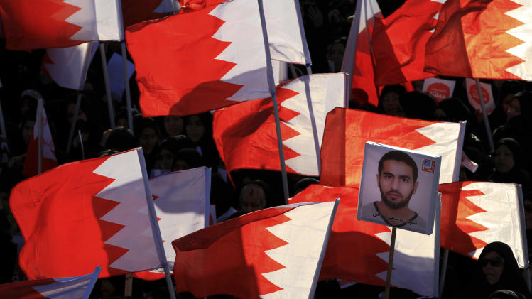 "Bahraini anti-government protesters wave national flags and carry signs during a march called by several opposition groups to demand freedom for political prisoners and democracy, in Muharraq, Bahrain, on Monday Feb. 4, 2013. Arabic on the image at right reads, ""Martyr Yousef Mowali."" (AP Photo/Hasan Jamali)"
