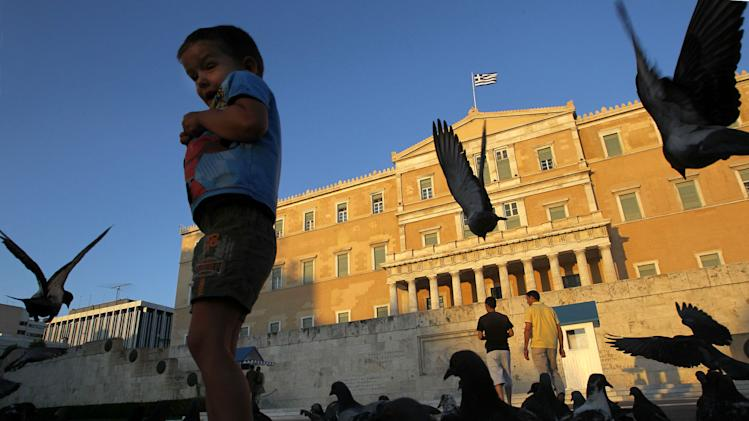A boy plays with pigeons in front of the Parliament in central Athens, Saturday, June 16, 2012. Greeks cast their ballots this Sunday for the second time in six weeks, after May 6 elections left no party with enough seats in Parliament to form a government and coalition talks collapsed. (AP Photo/Petros Karadjias)