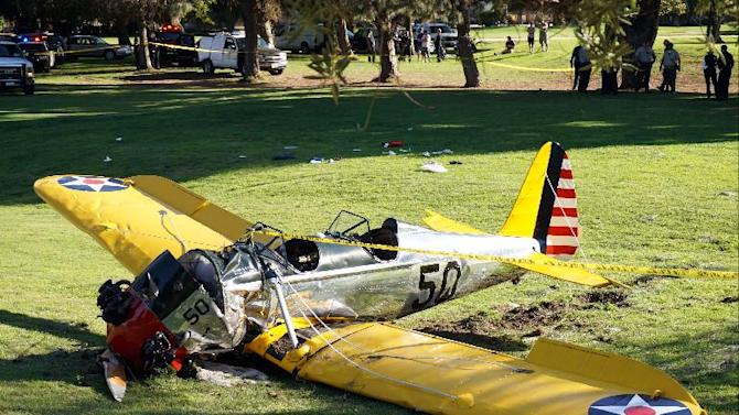 A small vintage airplane rests on the ground after it crash-landed on the Penmar Golf Course in the Venice area of Los Angeles, Thursday, March 5, 2015. Harrison Ford crash-landed the airplane shortly after taking off from a nearby airport and reporting engine problems. (AP Photo/Damian Dovarganes)