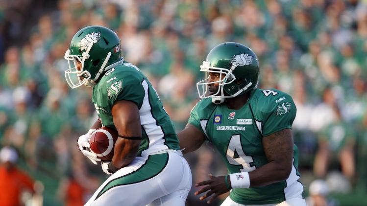 Roughriders quarterback Durant hands the ball off to running back Charles while playing against the Lions during the first half of their CFL football game in Regina