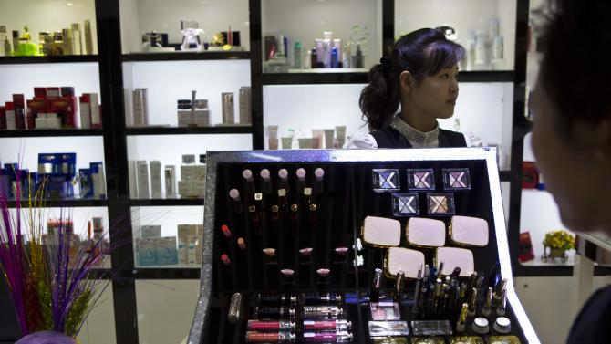 In this Sunday, May 19, 2013 photo, a North Korean woman works at a boutique shop which sells goods including Italian suits and Dior makeup at the newly-opened Haedanghwa Service Complex in Pyongyang, North Korea. U.N. sanctions are meant to stop the financing of North Korea's nuclear and missile programs but also aimed to sting the country's rich by crippling the import of luxury goods. (AP Photo/David Guttenfelder)