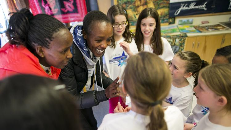 Marathoners Eunice Kirwa and Jemima Sumgong of Kenya count in Swahili with second-graders as elite runners from the Kenyan team meet students at Elmwood Elementary School in Hopkinton