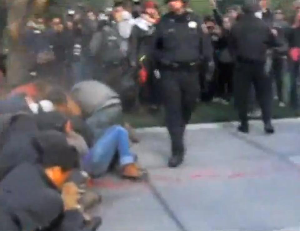 In this frame grab from video provided by Jamie Hall, a police officer pepper sprays Occupy demonstrators Friday, Nov. 18, 2011, at the University of California, Davis. (AP Photo/Jamie Hall)