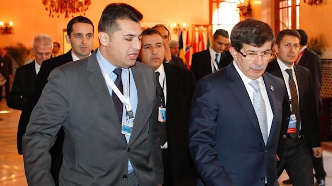"Turkish Foreign Minister Ahmet Davutoglu, right, arrives with other members of the Turkish delegation at a meeting of the Friends of the Syrian People in Marrakech, Morocco, Wednesday Dec. 12, 2012. The Syrian opposition called for ""real support"" and not just recognition on Wednesday, hours after the U.S. declared its new coalition was the ""legitimate representative"" of its country's people.  (AP Photo/Abdeljalil Bounhar)"