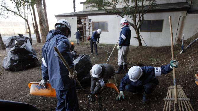 In this Wednesday, March 6, 2013 photo, workers pick up radiation-contaminated leaves during a cleanup operation in the abandoned town of Naraha, just outside the exclusion zone surrounding the Fukushima Dai-ichi nuclear plant in Japan. Two years after the triple calamities of earthquake, tsunami and nuclear disaster ravaged Japan's northeastern Pacific coast, radioactive and chemical contamination remains a threat. (AP Photo/Greg Baker)