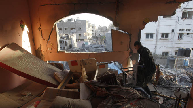 A Palestinian man picks up belongings from the rubble of a destroyed house after an Israeli airstrike in the Jabaliya refugee camp, northern Gaza Strip, Sunday, Nov. 18, 2012. The Israeli military widened its range of targets in the Gaza Strip on Sunday to include the media operations of the Palestinian territory's Hamas rulers, sending its aircraft to attack two buildings used by both Hamas and foreign media outlets. (AP Photo/Hatem Moussa)