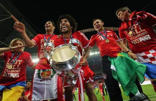 Bayern Munich's Dante of Brazil, centre,  holds the trophy as he reacts with teammates, after winning the Champions League Final against Borussia Dortmund , at Wembley Stadium in London, Saturday May