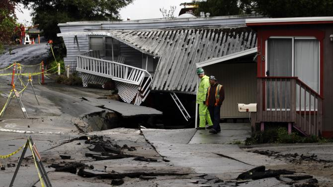 Workers survey storm damage at the Pacific Cove Mobile Home Park in Capitola, Calif., Friday, March 25, 2011. A powerful storm swept across California flooding part of Capitola, in Santa Cruz County, and forcing dozens of mobile homes residents to evacuate. The storm soaked hillsides along the coast threatening landslides as the rain continues. (AP Photo/Marcio Jose Sanchez)