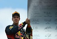 Red Bull Racing&#39;s German driver Sebastian Vettel celebrates on the podium at the Hockenheimring circuit during the German Formula One Grand Prix. Fernando Alonso extended his lead in this year&#39;s Formula One drivers&#39; world championship on Sunday when he drove to a flawless victory for Ferrari in the German Grand Prix