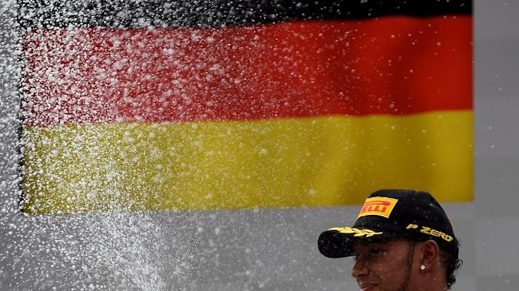 Lewis Hamilton celebrates celebrates after placing third in the German Formula One Grand Prix in Hockenheim on July 20, 2014