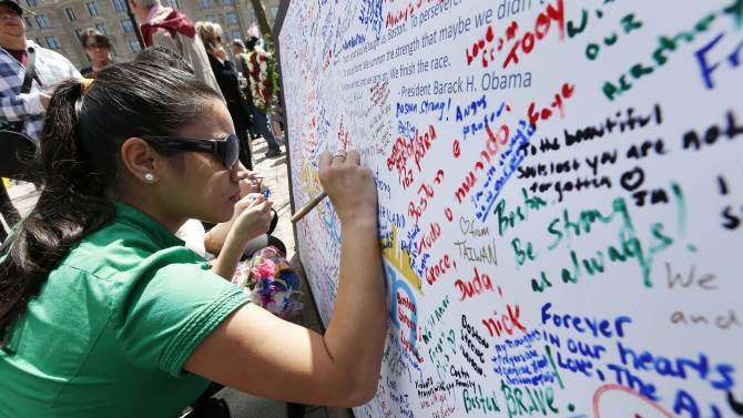 Michelle Littke, of Scituate, Mass., wites on a poster at a makeshift memorial in Copley Square on Boylston Street in Boston, Wednesday, April 24, 2013. Traffic was allowed to flow all the way down Boylston Street on Wednesday morning for the first time since two explosions on April 15.(AP Photo/Michael Dwyer)