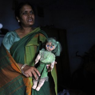A yoga teacher holds a doll belonging to her missing fifteen-year-old daughter inside her house in New Delhi